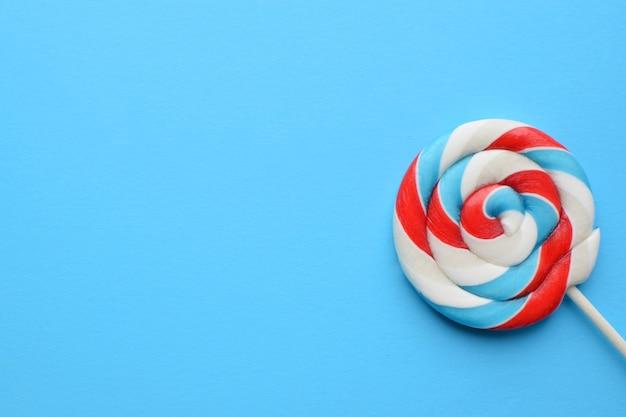 Pirulito multicolorido sobre um fundo azul. conceito de alimentos pouco saudáveis, açúcar, doces e doces.
