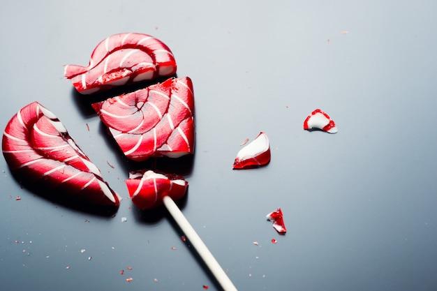 Pirulito quebrado em forma de coração em um fundo escuro com espaço de cópia