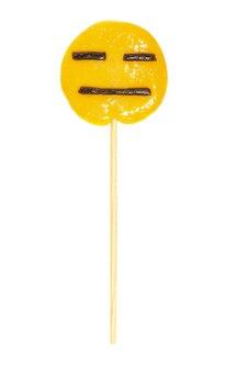 Pirulito redondo amarelo em um palito com uma cara de indiferença isolado em um fundo branco