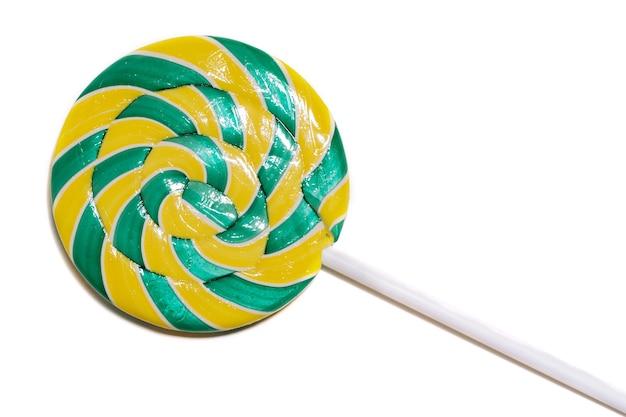 Pirulito verde-amarelado brilhante redondo em forma de espiral isolada em um fundo branco