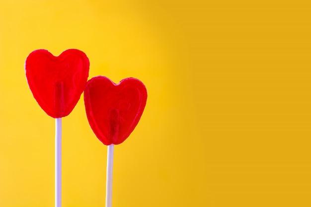 Pirulito vermelho com forma de coração na superfície amarela amo o conceito dia dos namorados.