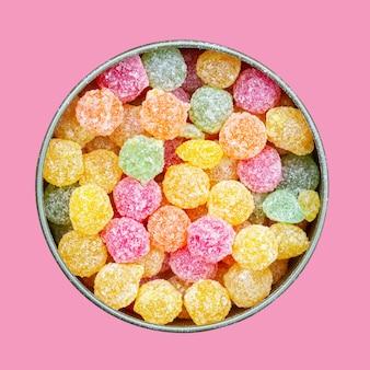 Pirulitos coloridos de montpensier dos doces de sucção coloridos em uma caixa de lata redonda isolada na cor-de-rosa