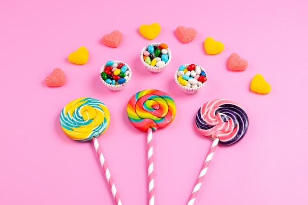 Pirulitos coloridos de uma vista frontal em palitos de palha doce rosa-branco, juntamente com marmeladas em forma de coração e doces coloridos em rosa