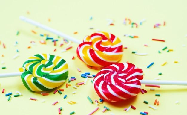 Pirulitos coloridos e confetes em fundo amarelo. doces para festa. açúcar
