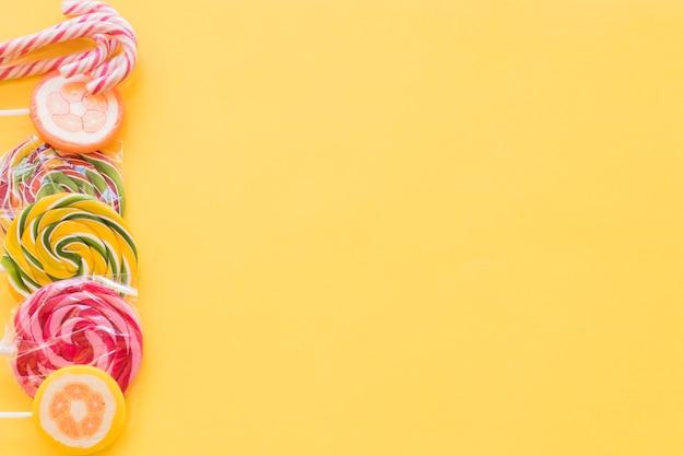Pirulitos coloridos e doces de bengala de natal em pano de fundo amarelo