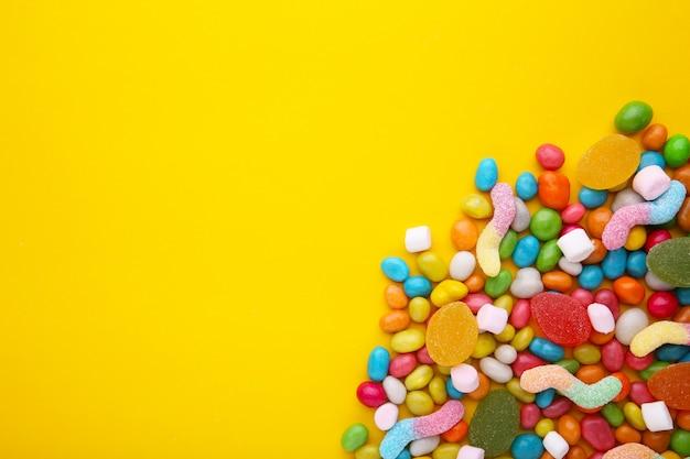 Pirulitos coloridos e doces redondos coloridos diferentes em fundo amarelo