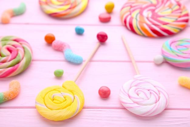 Pirulitos coloridos e doces redondos coloridos diferentes no fundo de madeira rosa