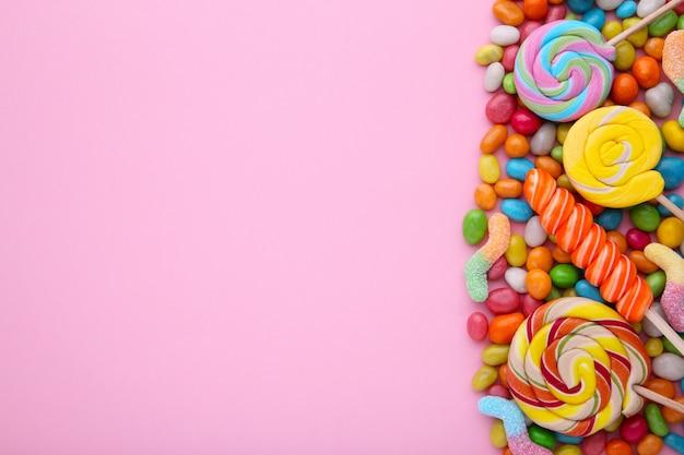 Pirulitos coloridos e doces redondos coloridos diferentes no fundo rosa