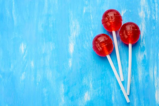Pirulitos de três bolas vermelhas em paus brancos