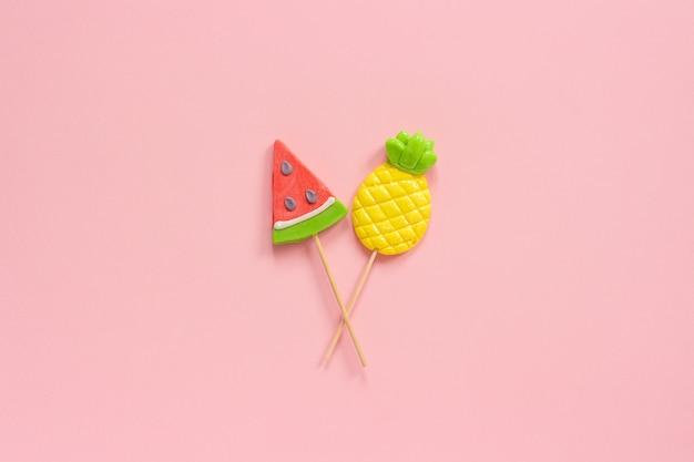 Pirulitos do abacaxi e da melancia na vara no fundo cor-de-rosa. conceito férias de verão ou feriados