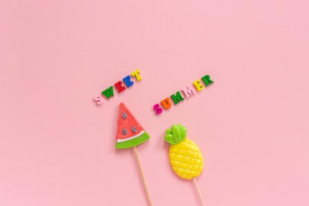 Pirulitos doces do texto, do abacaxi e da melancia do verão.