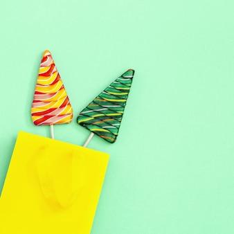 Pirulitos em forma de árvore de natal em uma sacola de papel para presente