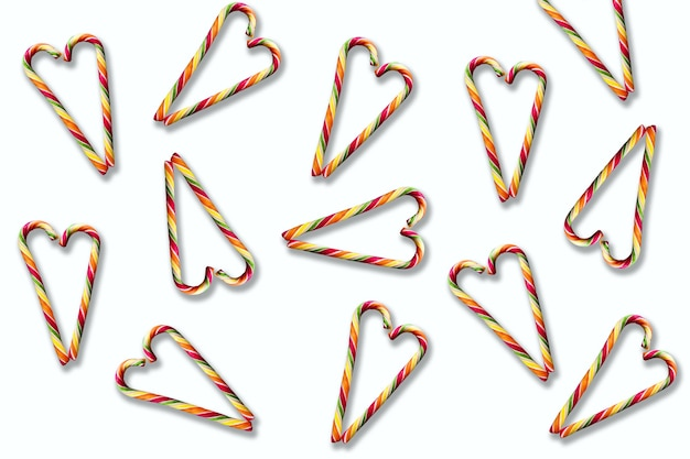 Pirulitos em forma de coração listrados multicoloridos em um fundo branco. natal, ano novo, dia dos namorados, clima de férias de inverno para os amantes