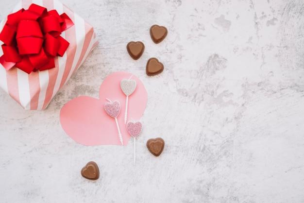 Pirulitos perto de doces doces de chocolate, coração de papel e caixa de presente