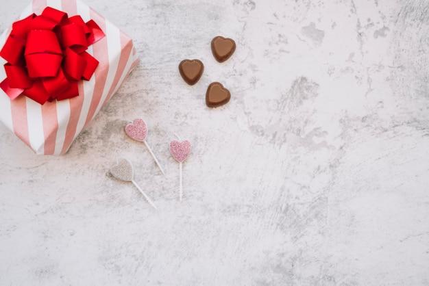 Pirulitos perto de doces doces de chocolate e caixa de presente