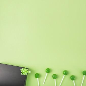 Pirulitos verdes com caixa de presente preta e arco sobre fundo verde