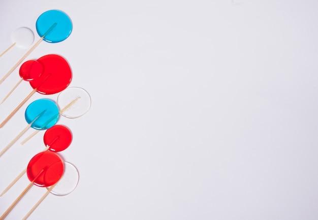 Pirulitos vermelhos, azuis, brancos coloridos no fundo branco. vista do topo. copie o espaço.