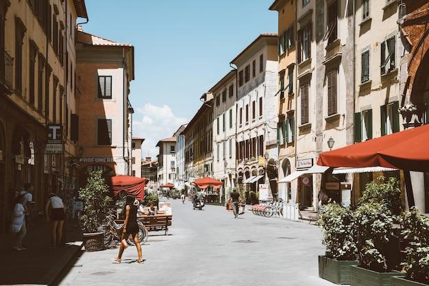 Pisa, itália - 29 de junho de 2018: caminhando na rua borgo stretto, na cidade de pisa, com edifícios históricos e lojas. as pessoas caminham e descansam. dia ensolarado de verão e céu azul