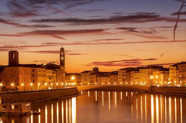 Pisa, região da toscana, itália. a ponte ponte di mezzo sobre o rio arno ao pôr do sol dourado à noite