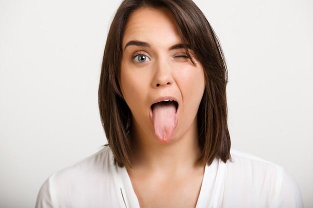Piscadela engraçada da mulher e mostra a língua