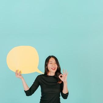 Piscando mulher com bolha de fala gesticulando ok