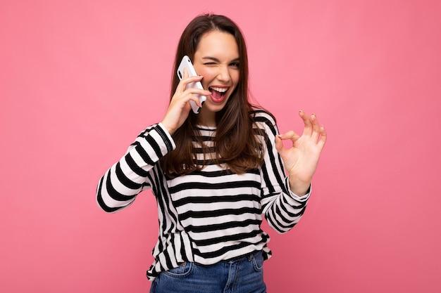Piscando mulher jovem muito feliz falando ao telefone, vestindo uma blusa listrada isolada sobre um fundo com espaço de cópia, mostrando o gesto de ok olhando para a câmera.