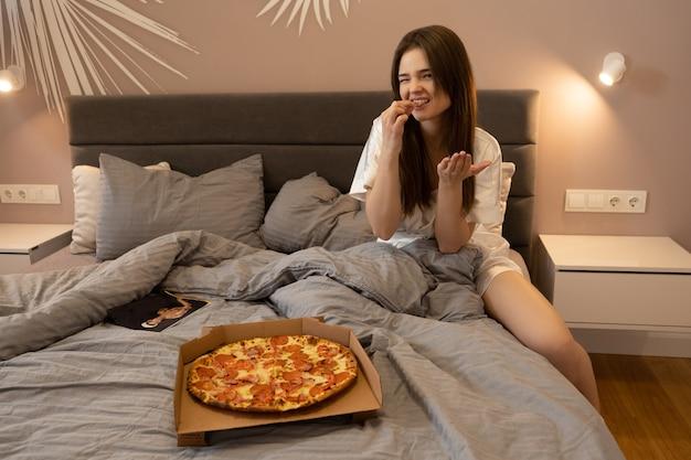 Piscando uma garota europeia sentada na cama e comendo pizza em casa. mulher jovem e bonita. cartaz de homem nu e caixa de papelão com pizza na cama. interior do quarto em apartamento moderno