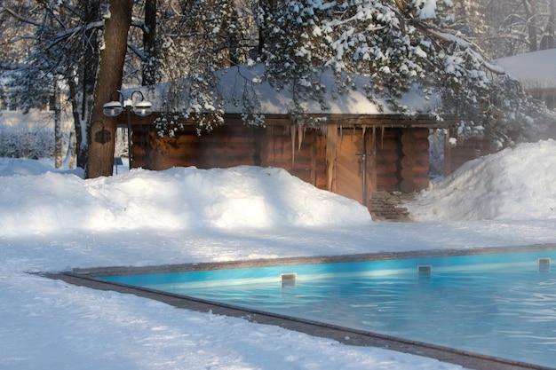 Piscina aquecida com água azul e banho russo de madeira no inverno ensolarado, ao ar livre.
