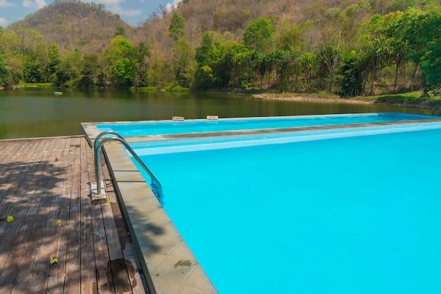 Piscina azul com piso de madeira perto da montanha do lago