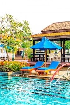 Piscina cama e guarda-chuva ao redor da piscina no hotel resort