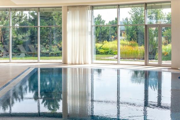 Piscina coberta em mansão luxuosa com janelas com vista para o parque verde de verão