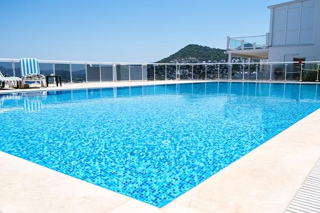 Piscina com água de cor turquesa no hotel ou aldeia de férias em dia de sol.