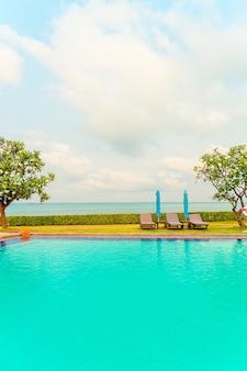 Piscina com cadeiras e guarda-sol ao redor da piscina com mar oceano