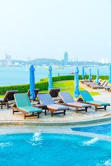 Piscina com cadeiras e guarda-sol ao redor da piscina com vista para o mar