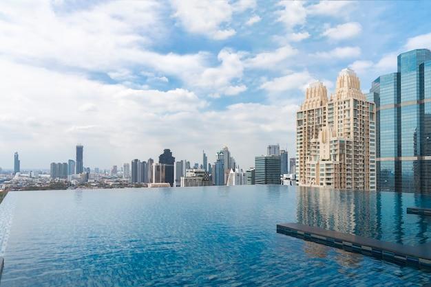 Piscina com edifício moderno no centro da cidade do negócio e no céu azul no dia ensolarado.