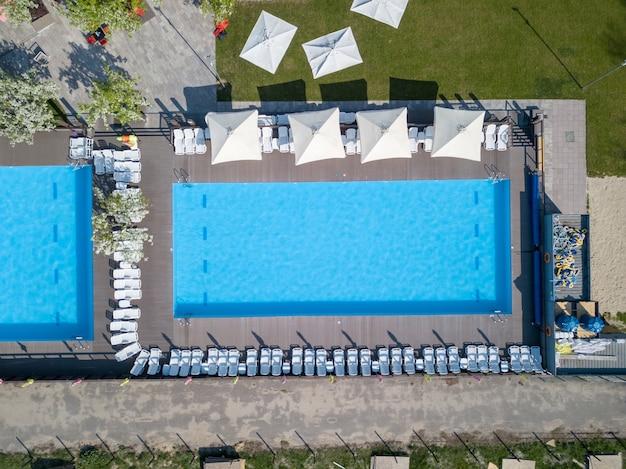 Piscina de água azul no verão e camas de praia brancas com elemento externo