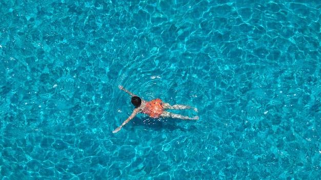 Piscina de água clara de cor azul e pessoas desfrutando em dia ensolarado de verão e ângulo de visão superior.