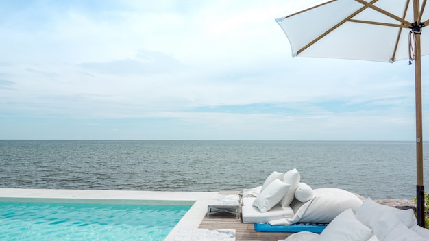 Piscina de luxo e água azul no resort com linda vista para o mar.
