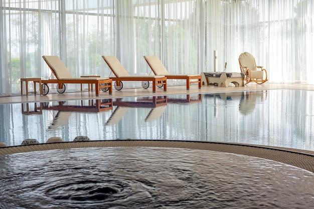 Piscina interior confortável com espreguiçadeiras, espreguiçadeiras, cama de massagem e cadeira de balanço no campo.