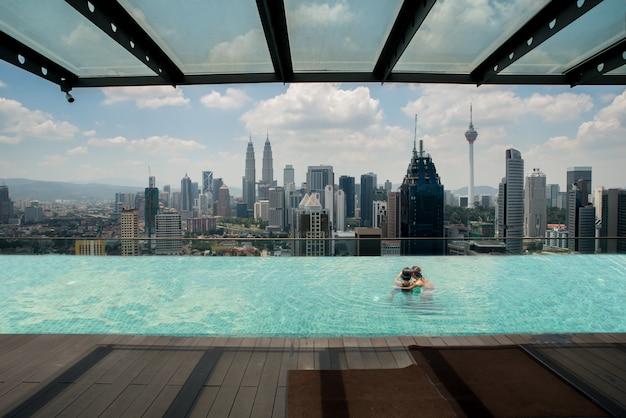 Piscina na parte superior do telhado com opinião bonita kuala lumpur da cidade, malásia.