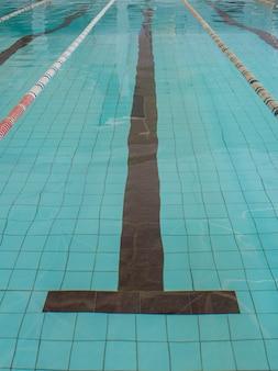 Piscina vazia com água azul clara. linha de marcação central visível