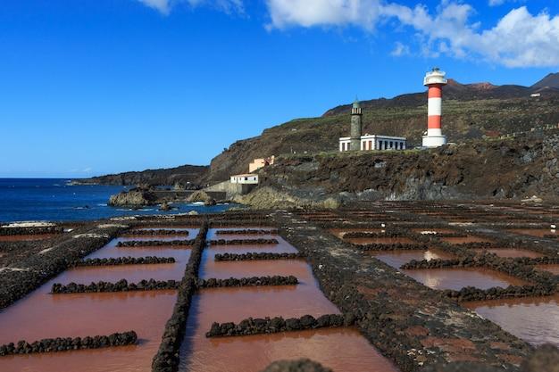Piscinas vulcânicas na fabricação de sal com farol e montanhas