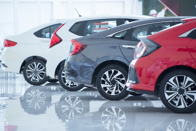 Piso branco para estacionamento de carros novos, fotos de carros novos no showroom, parque, show em espera pelas vendas de revendedores da filial e novos centros de serviços de automóveis