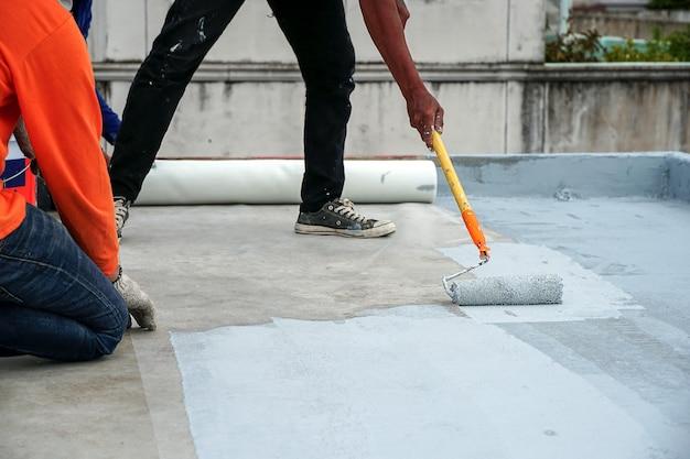 Piso cinza pintado à mão com rolos de pintura para rede de reforço à prova d'água reparo à prova d'água