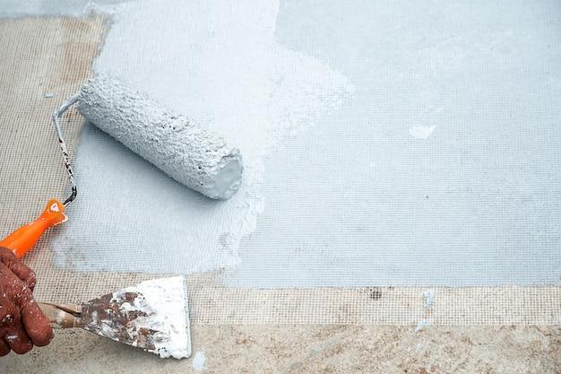 Piso cinza pintado à mão com rolos de pintura para rede de reforço à prova d'água