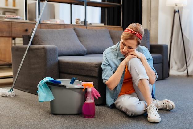 Piso de carpete. mulher madura bonita, doente e cansada, apoiada em uma perna enquanto limpa o equipamento ao redor