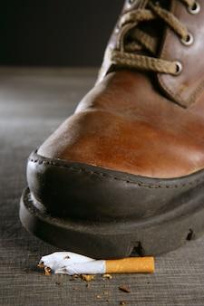 Piso de cigarro quebrado por uma bota