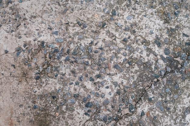 Piso de cimento com pequenas pedras parede ou piso de concreto cinza velho rachado e sujo