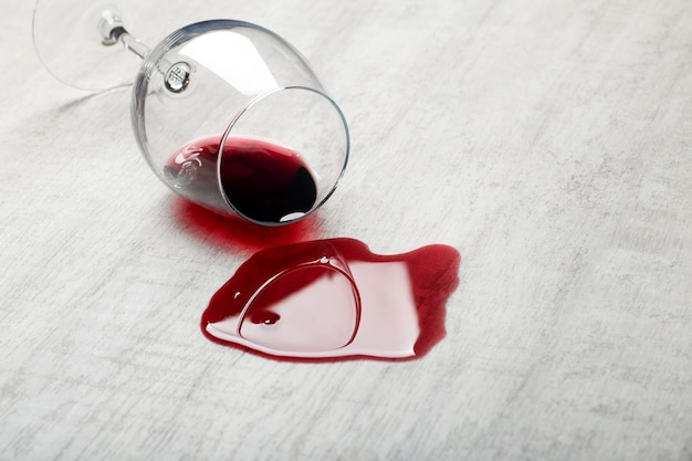 Piso de madeira com copo de vinho tinto virado. vinho derramado em piso de parquete laminado de madeira com proteção contra umidade.