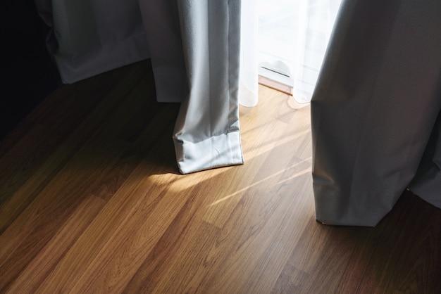 Piso de madeira com forte luz do sol através da cortina da sala de estar